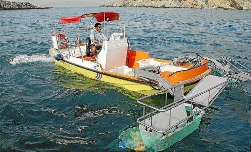 Imagen de archivo de un trabajador del servicio de limpiezas de litoral trabajando en aguas de Ibiza.