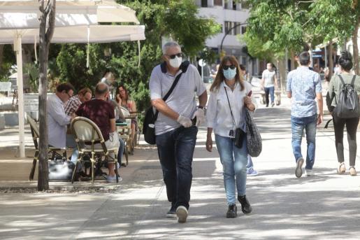 Dos personsa pasean por Vila con sus mascarillas puestas.