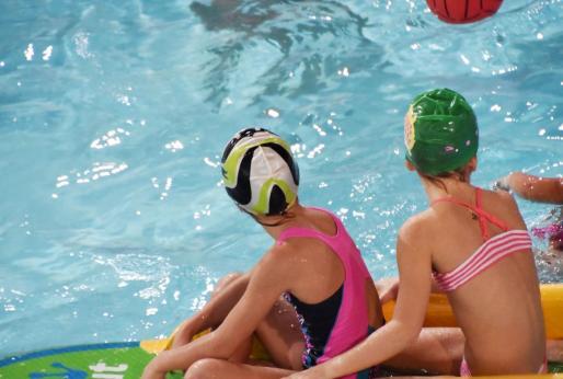 Dos jóvenes juegan en una piscina.