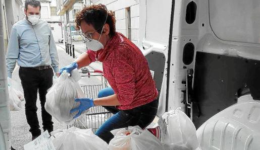 Personal de Cáritas cargando alimentos en una furgoneta.