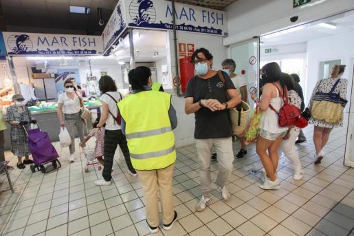 Varias personas, en el Mercat Nou, de compras.