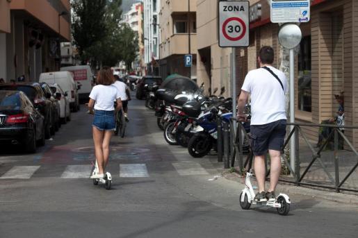 Dos personas utilizando un patinete eléctrico en Ibiza.