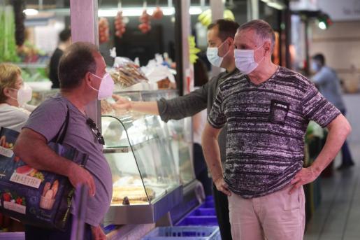 Una imagen tomada en el Mercat Nou con los clientes ataviados con mascarilla.