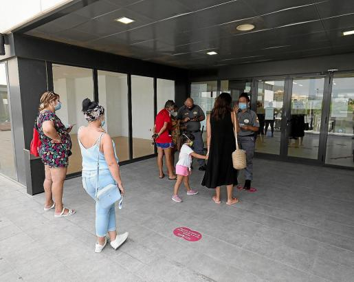 Varias personas esperan en la entrada del SOIB.