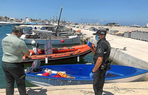 Imagen de dos agentes custodiando en la Savina la embarcación localizada en s'Estufador.
