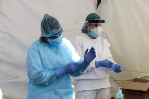 Sanitarios colocándose los elementos de protección.