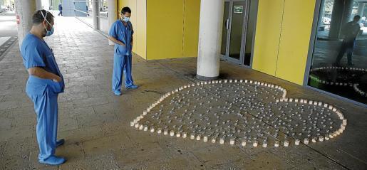 Dos trabajadores de Son Espases ante un corazón hecho con velas en recuerdo a los que han fallecido por coronavirus.