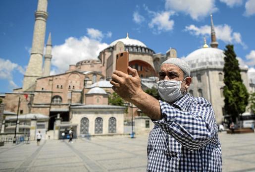 Un hombre se hace un selfie en Estambul con la mascarilla puesta.