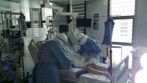 Dos sanitarios retiran la respiración mecánica a un enfermo de coronavirus que ha mejorado.