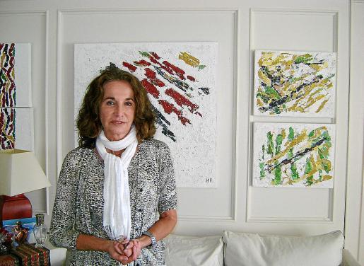 Herminia Romero con algunas de sus obras al fondo.