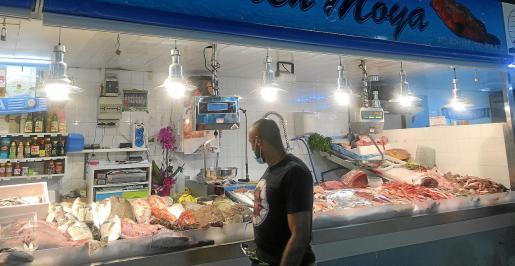 Un hombre observa el expositor de una pescadería del Mercat Nou.