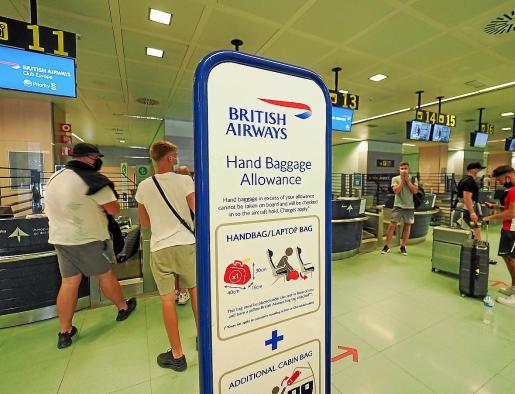 Cartel de British Airways y varios turistas ingleses esperando en el aeropuerto.