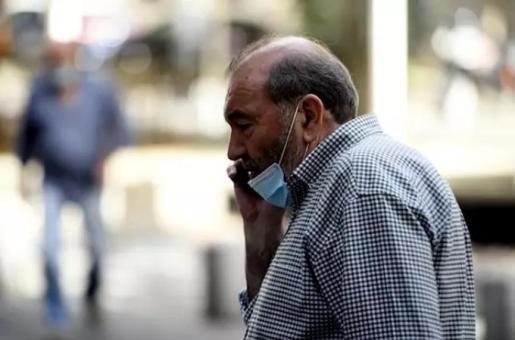 Un hombre con mascarilla habla por teléfono en la calle, en Madrid (España) a 30 de julio de 2020. - Óscar Cañas - Europa Press