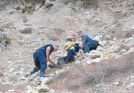 Agentes de la Policía Local de Santa Eulària y de la Guardia Civil descienden a uno de los pequeños que quedaron en un punto sin retorno junto a sus padres.