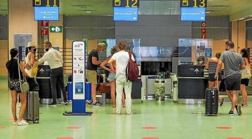 Varios viajeros ingleses esperan para facturar en el aeropuerto de Ibiza al día siguiente de anunciarse la cuarentena.