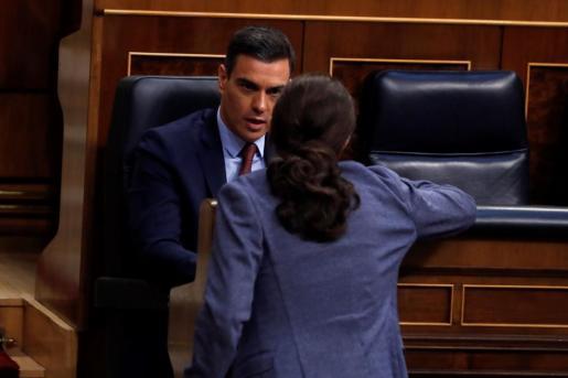 El presidente del Gobierno, Pedro Sánchez, conversando con el vicepresidente tercero, Pablo Iglesias, en el Congreso.