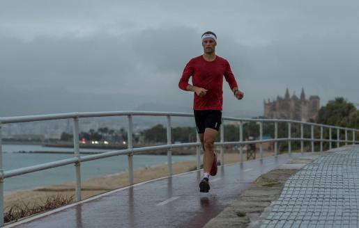 Un hombre corre bajo la lluvia por el paseo de la Playa de Can Pere Antoni de Palma.