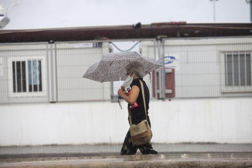 Una mujer se cubre con un paraguas en Ibiza.