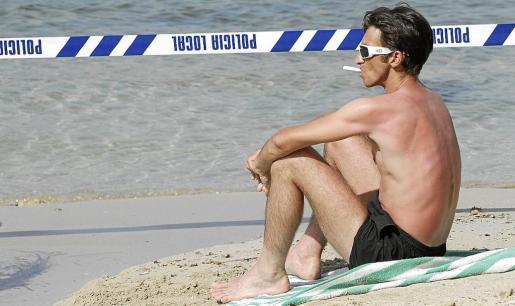 Un bañista sigue tomando el sol en la cala pese a que la cinta policial advierte del peligro por el vertido.