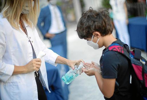 Una docente toma la temperatura y da gel a un alumno en un centro de Barcelona.