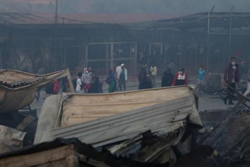Los migrantes caminan entre los restos de su refugio tras el incendio.