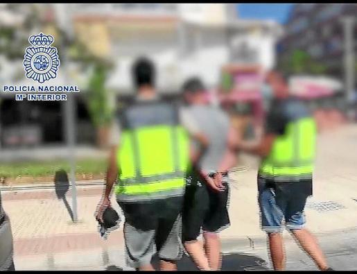 Dos agentes de la Policía Nacional custodian al fugitivo detenido.