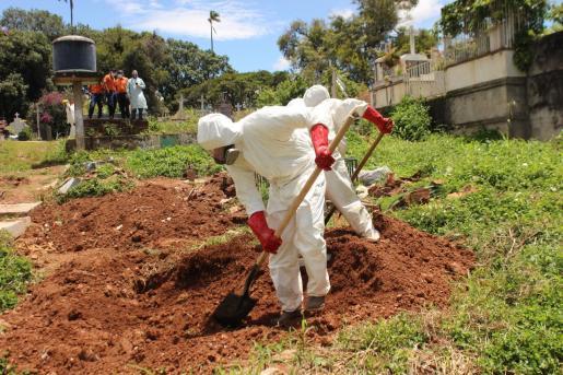 Trabajadores gubernamentales entierran en Venezuela a una persona que falleció de COVID-19.