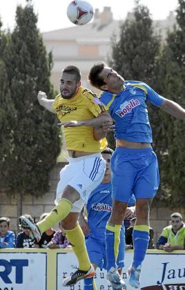 Carlos Fernández pelea por un balón aéreo junto a un rival.
