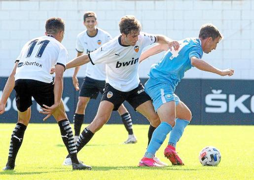 Javi Pérez, de la UD Ibiza, protege el balón ante la presión de un jugador valencianista.