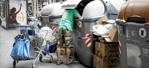 Un hombre mirando dentro de un contenedor de basura.