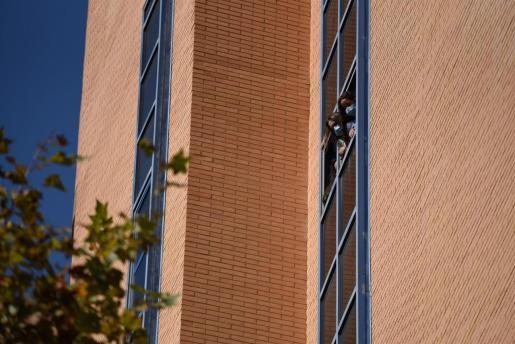 Dos estudiantes se asoman a una ventana de la residencia Galileo Galilei durante una concentración convocada por el sindicato 'Estudiantes en Lucha' en la residencia Galileo Galilei, en Valencia.