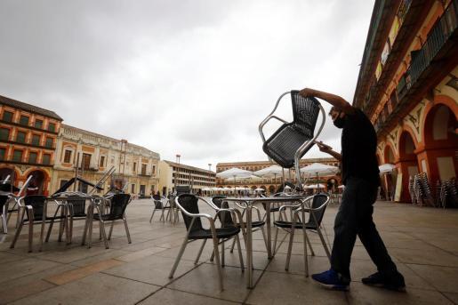 El trabajador prepara la terraza de un bar en Córdoba este domingo.