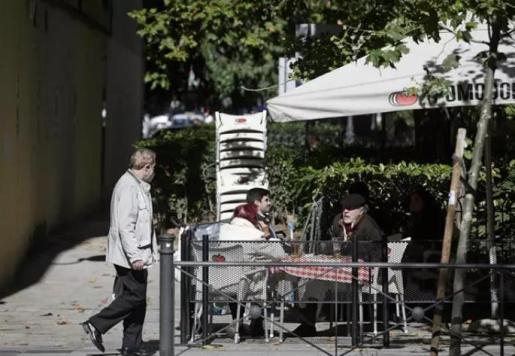 Un hombre camina frente a la terraza de un bar donde hay sentadas otras tres personas en la zona básica de salud de Guzmán el Bueno, en el distrito de Chamberí, en Madrid (España), a 26 de octubre de 2020. - Óscar Cañas - Europa Press