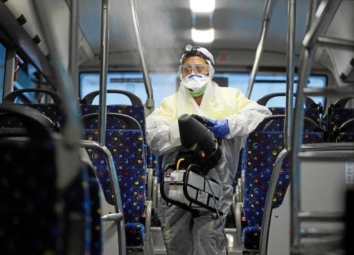 Una empleada de Alsa realiza la nebulización semanal de uno de los autobuses.