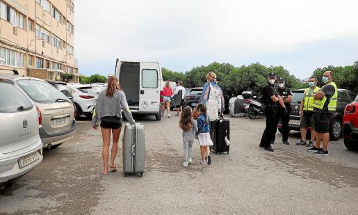 Una familia sale de su hogar en la escalera 1 de los apartamentos Don Pepe tras el desalojo en 4 de junio.
