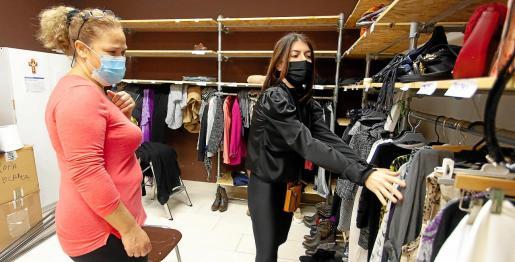 Una de las alumnas mira ropa, ayudada por una de las voluntarias de Cáritas.