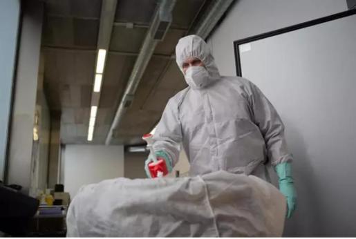 Un operario del Crematorio de Girona desinfecta el cuerpo de una persona fallecida con COVID-19 y su ataúd, antes de introducirle en el horno crematorio.