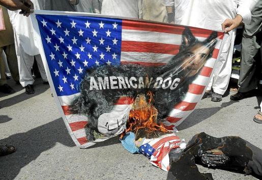 Manifestantes queman fotos de Obama y banderas de EEUU en una protesta en contra del vídeo sobre Mahoma en Peshawar.