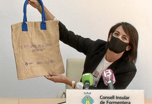 Ana Juan, consellera de Comercio, muestra una de las bolsas reutilizables que regalarán las tiendas