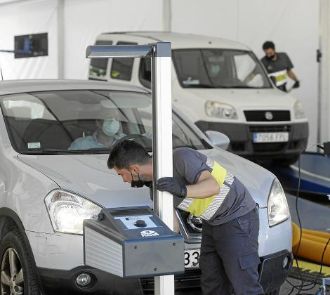 Un operario de la ITV móvil ubicada en el Recinto Ferial revisa un vehículo.