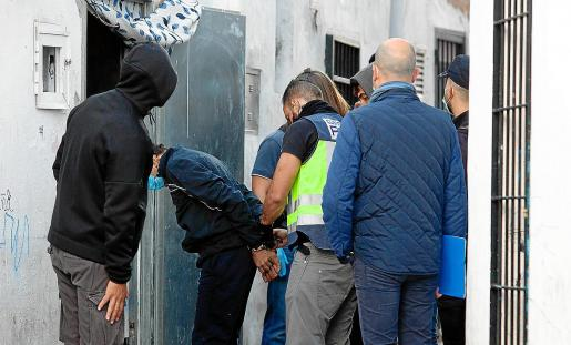 Agentes de la Policía Nacional esposan a uno de los detenidos en la calle Alt.