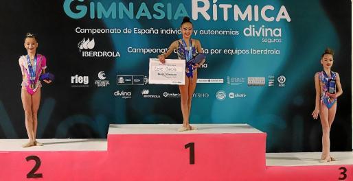 Leire García posa con sus dos medallas y la beca de Divina Pastora en lo más alto del podio.