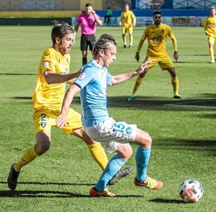 Javi Lara, de la UD Ibiza, protege el balón ante la presión de Pina, del Orihuela, en un lance del partido de ayer.