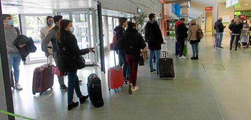 Viajeros, en su mayoría estudiantes, guardan cola ayer para entrar en la terminal del aeropuerto de es Codolar.
