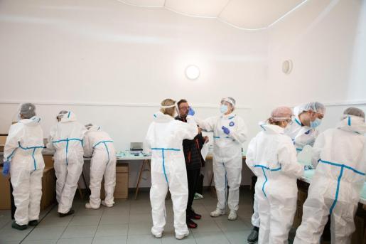Un grupo de sanitarios, con los trajes de protección contra la COVID-19, realizando pruebas de coronavirus en Menorca.