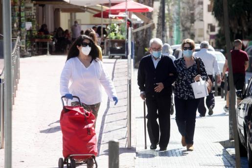 Gente en las calles de Ibiza utilizando mascarilla.