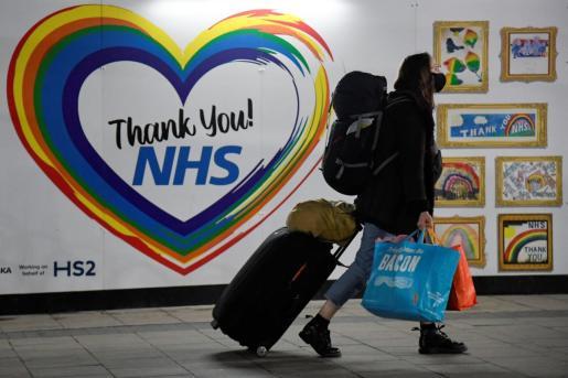 Una viajera pasa frente a un cartel de agradecimiento a los sanitarios en una estación de tren del Reino Unido.