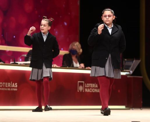 Dos de las niñas de la residencia de San Ildefonso, Judith García Benítez (i) y Nerea Pareja Martínez (d) cantan el segundo premio de la Lotería de Navidad, el 52.472.