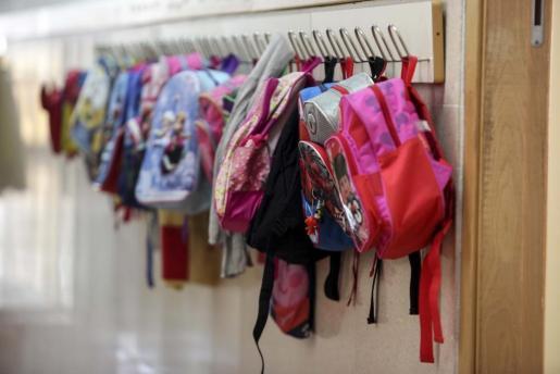 Mochilas que cuelgan en un pasillo de un colegio de Ibiza.