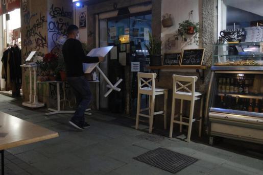 Un camarero recoge las mesas de la terraza de una cafetería en Palma.